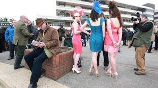 A male racegoer appears uninterested with the fashion show going on behind him.