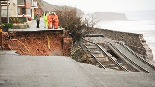 Workmen assess a huge hole exposing ground services and exposed railway track after the sea wall collapsed in Dawlish.