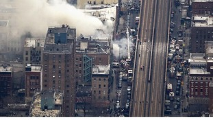 Smoke billows from the site of a building collapse
