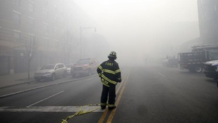 A firefighter stands in smoke filled East 116th street