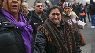 A woman cries as she is brought to the site of a building collapse in Harlem