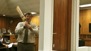 Forensic expert Johannes Vermeulen swings at a door with a cricket bat in court.
