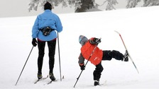 A mother and her child during cross-country skiing through the snowy countryside in the Black Forest, Germany.