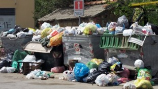 Piles of rubbish lie on a street in Cefalu in Italy