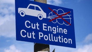 Sign asking motorists to switch of engines at railway level crossing.