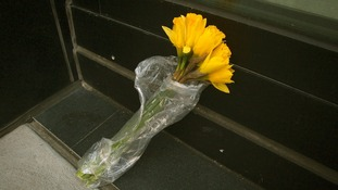 A lone bouquet of flowers sits on the ground outside the Manhattan apartment building.