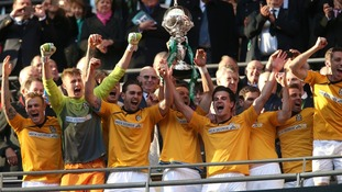 Cambridge United's players celebrate victory as they lift the FA Trophy after the match