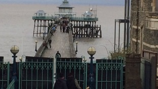 The band are seen with film crews halfway along the famous pier.