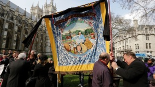The Durham Miners Association hoist a flag in Westminster.