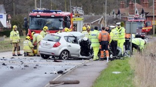 Emergency services in the road with wreckage of a silver car and two fire engines