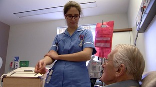 Nurse tending to old male patient