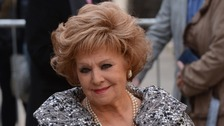 Barbara Knox smiling at camera with pearl necklace and grey patterned dress coat