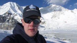 Alex Staniforth wearing a hat and glasses in the snowy mountains