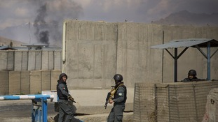 Afghan policemen take position while smoke from a burning building billows in the background.