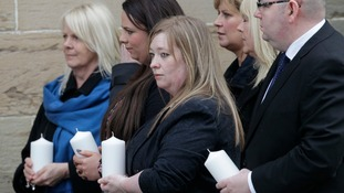 Members of the congregation hold candles outside the memorial service.