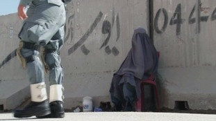 Detective Nugis wears a burqa as she carries out inspections at a roadblock in Kandahar.