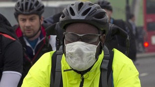 A cyclist wears a mask as he crosses London bridge in the smog this morning.