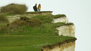 Two sightseers stand at the top of Birling Gap, near Eastbourne, East Sussex.