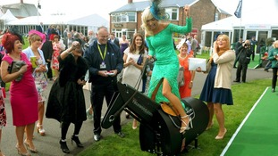One racegoer takes a ride a model horse during Ladies Day.