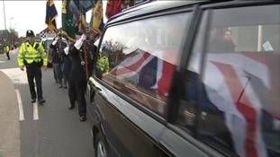 Protestors march behind an empty coffin