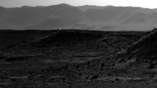 A speck of light can be seen flaring upwards from the hillside on Mars.