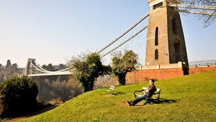 A man relaxes in the sun by Isambard Kingdom Brunel's famous Clifton Suspension Bridge.
