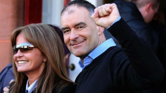 Tommy Sheridan accompanied by his wife Gail, salutes well wishers as he arrives home in Glasgow after leaving prison.