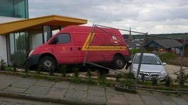 Post van on two wheels after crashing into building