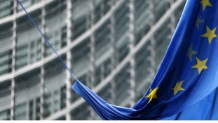 An EU flag hangs outside the European Commission headquarters in Brussels