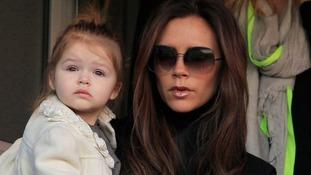 Victoria Beckham and daughter Harper watch David Beckham play for Paris Saint-Germain in March 2013.