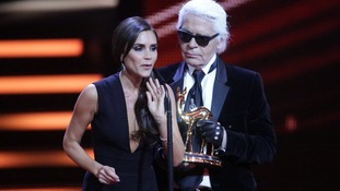 Victoria Beckham is awarded a Bambi trophy for fashion from fellow designer Karl Lagerfeld in November 2013.
