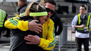 A runner at the Boston Marathon last year is comforted after the explosions.