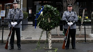 Honour guards stand beside a wreath at the site of one of the two bomb blasts that took place during last year's Boston Marathon.
