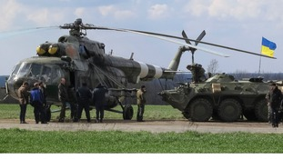 Ukrainian troops near a MI-8 military helicopter and armoured personnel carrier at a checkpoint in east Ukraine.