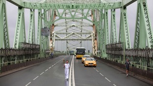 Torchbearer carries the Olympic Flame over Runcorn Bridge