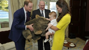 Prince George, with his parents Their Royal Highnesses The Duke and Duchess of Cambridge, receives a gift from the Governor-General