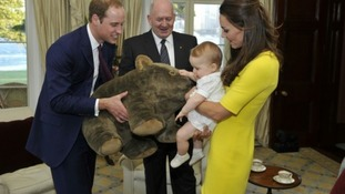 Prince George, with his parents, receives a gift from the Governor-General.