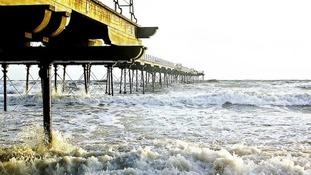tide crashing against pier and beach at Saltburn