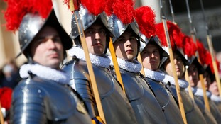 Swiss guards stand to attention before the arrival of Pope Francis to lead the Easter mass in Saint Peter's Square.