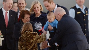 Prince George receives a gift after landing in Canberra.
