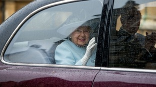 The Queen waves to crowds as she and the Duke of Edinburgh arrive at Windsor Castle for the Easter Sunday service.