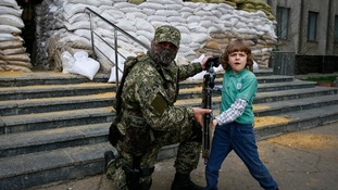 A pro-Russian insurgent poses for a photo with a child in Slaviansk.