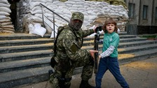 An armed pro-Russian poses for a photo with a child in Slaviansk.