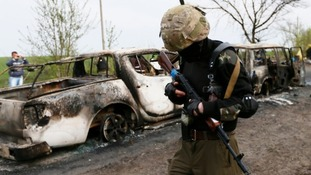 Pro-Russian militant walks past burnt cars near a checkpoint in Slaviansk.