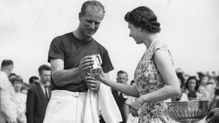 Queen Elizabeth II presents a tankard to her husband after his team won a polo match