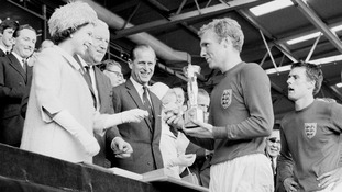 England captain Bobby Moore holding the Jules Rimet Trophy, he collected from the Queen