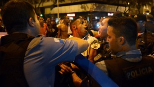 A resident reacts as he is detained by police during the protests.