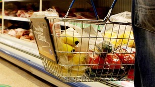 A man in a supermarket with veg and fruit in his basket.