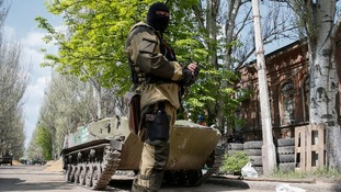 A pro-Russian armed man stands guard near the state security service building in Slaviansk