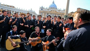 Priests sing in Saint Peter's Square at the Vatican ahead of the canonisation ceremony tomorrow.